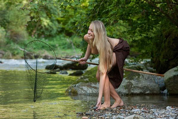 Нагая нимфа ловит рыбу в реке