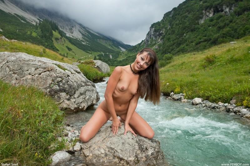 Голая баба хвастается накачанным телом на речном булыжнике в горах