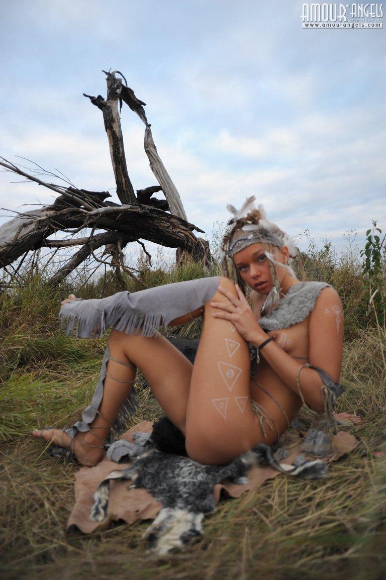 Дикая барышня в шкурах на природе снимается сидя у костра без лифчика