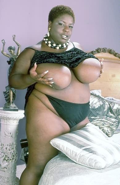 Черная особа женского пола с крупными грудями оголяет свое туловище и шокирует невероятными объемами